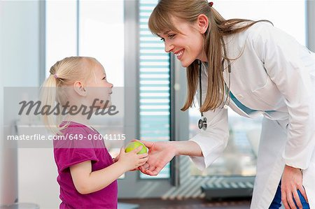 Doctor handing girl an apple in office Stock Photo - Premium Royalty-Free, Image code: 649-06041115