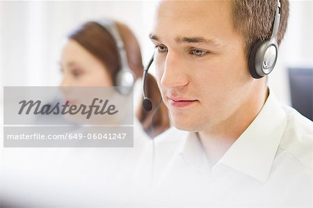 Business people working in headsets Stock Photo - Premium Royalty-Free, Image code: 649-06041247