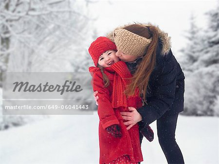 Mother and daughter kissing in snow Stock Photo - Premium Royalty-Free, Image code: 649-06041443