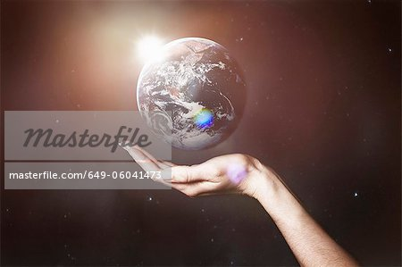 Hand holding image of the Earth Stock Photo - Premium Royalty-Free, Image code: 649-06041473