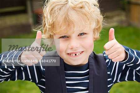 Smiling boy giving thumbs-up outdoors Stock Photo - Premium Royalty-Free, Image code: 649-06041770