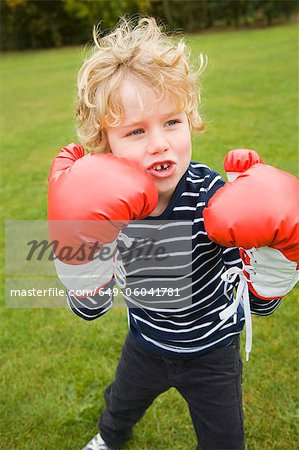 Boy playing with boxing gloves outdoors Stock Photo - Premium Royalty-Free, Image code: 649-06041781