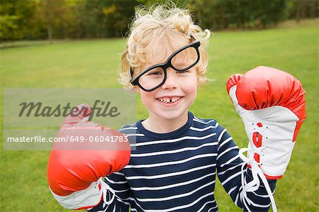 Boy playing with boxing gloves outdoors Stock Photo - Premium Royalty-Free, Image code: 649-06041783