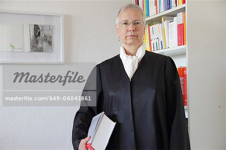 Lawyer holding text book in office Stock Photo - Premium Royalty-Free, Image code: 649-06041861