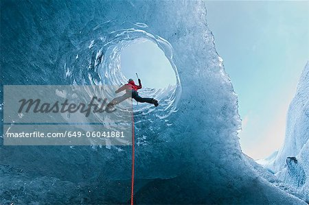 Climber climbing out of ice cave Stock Photo - Premium Royalty-Free, Image code: 649-06041881