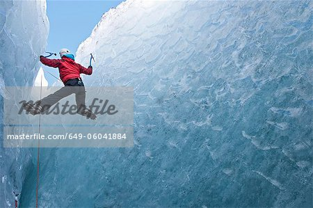 Climber climbing out of ice cave Stock Photo - Premium Royalty-Free, Image code: 649-06041884