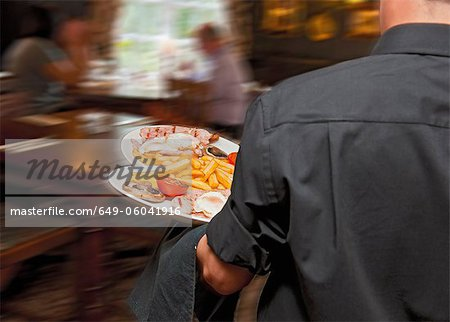Waiter carrying plates in restaurant Stock Photo - Premium Royalty-Free, Image code: 649-06041916