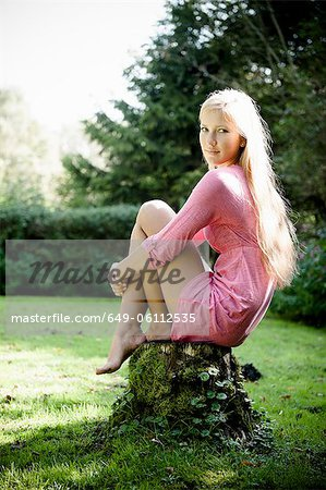 Woman sitting on stump outdoors Stock Photo - Premium Royalty-Free, Image code: 649-06112535