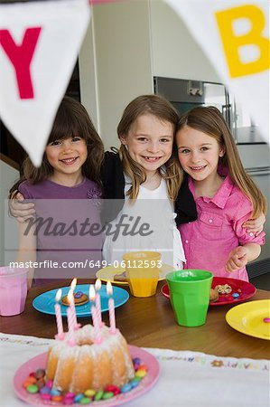 Smiling girls hugging at birthday party Stock Photo - Premium Royalty-Free, Image code: 649-06112593