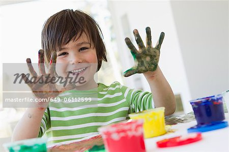 Smiling boy finger painting indoors Stock Photo - Premium Royalty-Free, Image code: 649-06112599
