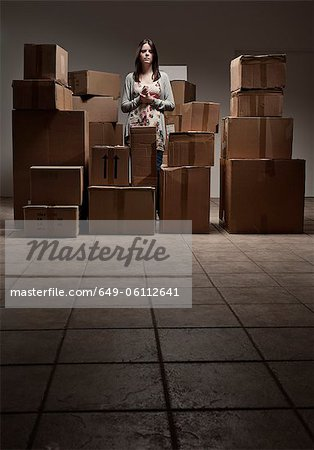 Teenage girl in pile of cardboard boxes Stock Photo - Premium Royalty-Free, Image code: 649-06112641