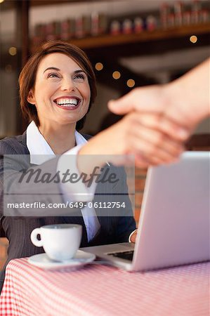Business people shaking hands in cafe Stock Photo - Premium Royalty-Free, Image code: 649-06112754
