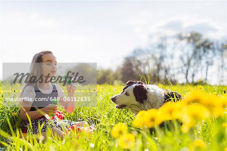 Girl blowing bubbles with dog in field Stock Photo - Premium Royalty-Free, Image code: 649-06112835