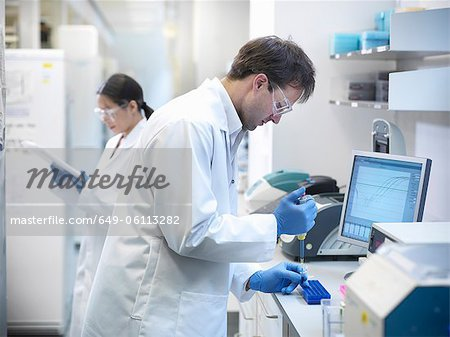 Scientists piping liquid into tubes Stock Photo - Premium Royalty-Free, Image code: 649-06113282