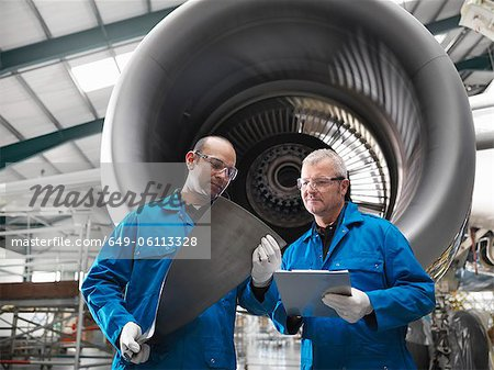 Workers talking in airplane hangar Stock Photo - Premium Royalty-Free, Image code: 649-06113328