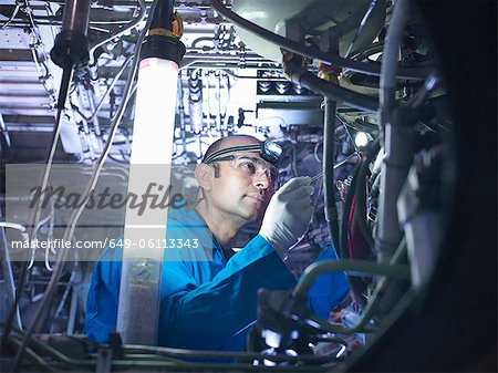 Worker adjusting airplane machinery Stock Photo - Premium Royalty-Free, Image code: 649-06113343
