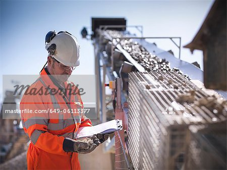 Worker with clipboard by conveyor belt Stock Photo - Premium Royalty-Free, Image code: 649-06113377