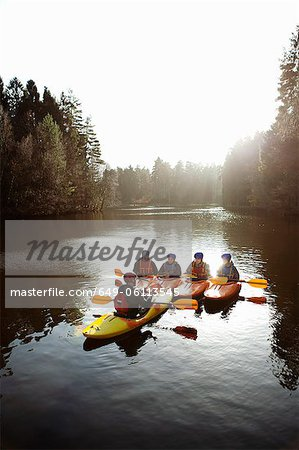 Teacher talking to students in kayaks Stock Photo - Premium Royalty-Free, Image code: 649-06113545