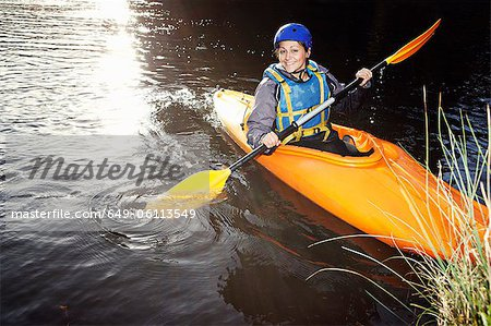 Kayaker rowing in still lake Stock Photo - Premium Royalty-Free, Image code: 649-06113549