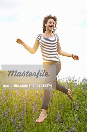 Woman leaping in tall grass Stock Photo - Premium Royalty-Free, Image code: 649-06113574