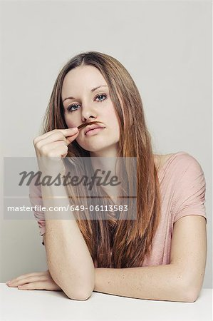 Woman playing with hair as mustache Stock Photo - Premium Royalty-Free, Image code: 649-06113583