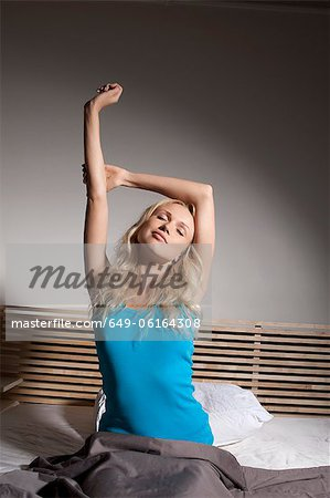 Smiling woman stretching in bed Stock Photo - Premium Royalty-Free, Image code: 649-06164308