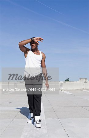 Man shielding his eyes on urban rooftop Stock Photo - Premium Royalty-Free, Image code: 649-06164469