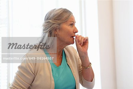 Older woman coughing into her hand Stock Photo - Premium Royalty-Free, Image code: 649-06164507