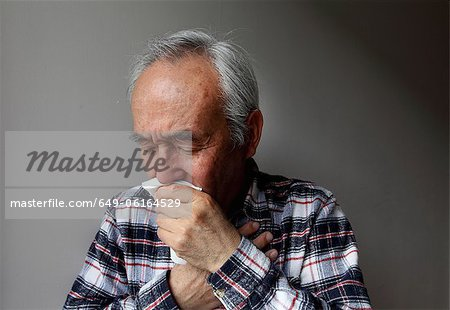 Older man coughing into napkin Stock Photo - Premium Royalty-Free, Image code: 649-06164529