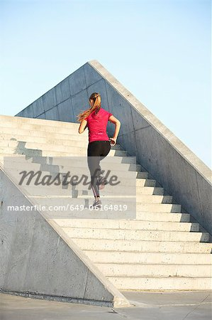 Woman running on staircase Stock Photo - Premium Royalty-Free, Image code: 649-06164819