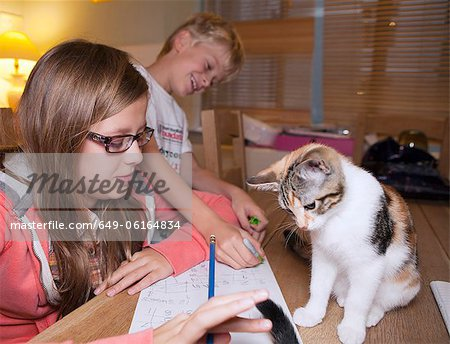Children with cat during homework Stock Photo - Premium Royalty-Free, Image code: 649-06164834