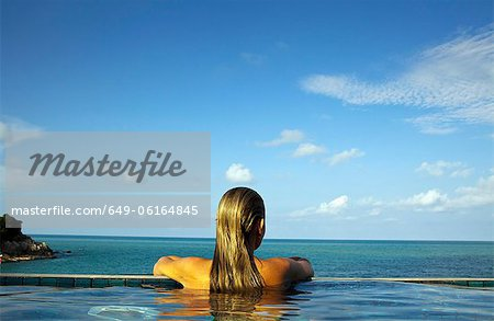 Woman relaxing in infinity pool Stock Photo - Premium Royalty-Free, Image code: 649-06164845