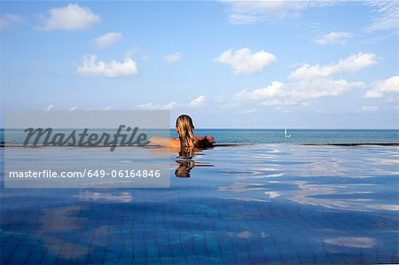 Woman relaxing in infinity pool Stock Photo - Premium Royalty-Free, Image code: 649-06164846