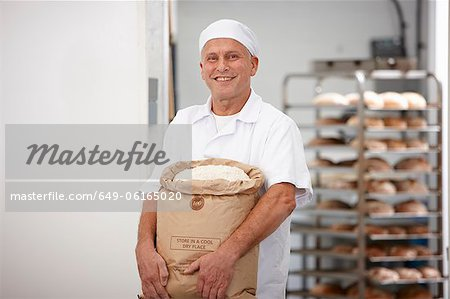 Chef carrying sack of flour in kitchen Stock Photo - Premium Royalty-Free, Image code: 649-06165020