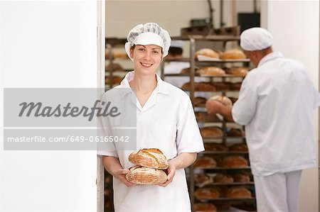 Chef holding loaves of bread in kitchen Stock Photo - Premium Royalty-Free, Image code: 649-06165042
