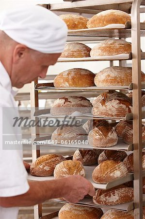 Chef putting tray of bread on rack Stock Photo - Premium Royalty-Free, Image code: 649-06165048