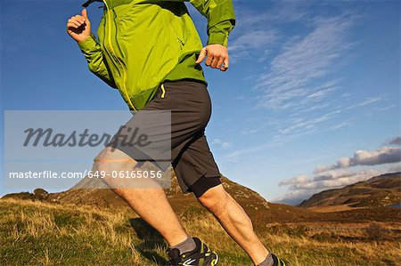 Hiker running up grassy hillside Stock Photo - Premium Royalty-Free, Image code: 649-06165056