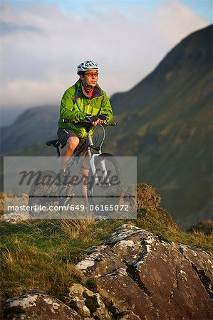 Mountain biker standing on hilltop Stock Photo - Premium Royalty-Free, Image code: 649-06165072