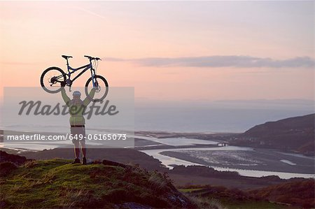 Man holding bicycle on hilltop Stock Photo - Premium Royalty-Free, Image code: 649-06165073