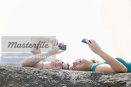 Teenage girls using cell phones outdoors