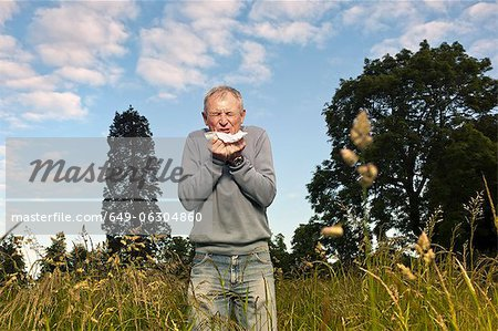 Man sneezing in tall grass Stock Photo - Premium Royalty-Free, Image code: 649-06304860