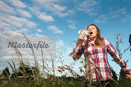 Woman sneezing in tall grass Stock Photo - Premium Royalty-Free, Image code: 649-06304861