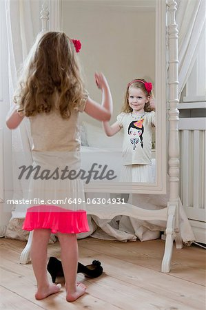 Girl admiring herself in mirror Stock Photo - Premium Royalty-Free, Image code: 649-06304931