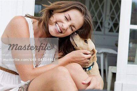 Smiling woman playing with dog Stock Photo - Premium Royalty-Free, Image code: 649-06304961