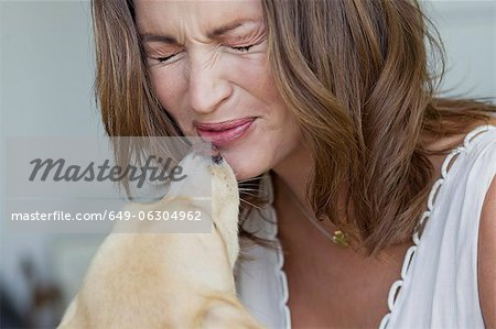 Smiling woman playing with dog Stock Photo - Premium Royalty-Free, Image code: 649-06304962