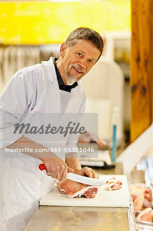 Butcher slicing meat at counter Stock Photo - Premium Royalty-Free, Image code: 649-06305046