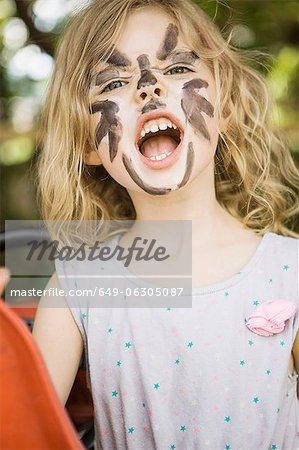 Girl wearing face paint outdoors Stock Photo - Premium Royalty-Free, Image code: 649-06305087