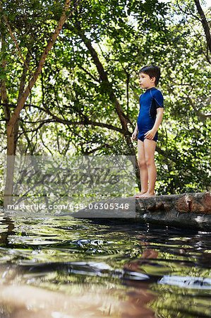 Boy standing by river in forest Stock Photo - Premium Royalty-Free, Image code: 649-06305348