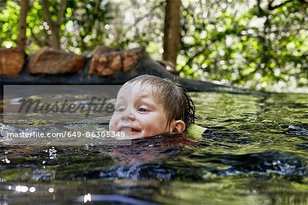 Boy swimming in river in forest Stock Photo - Premium Royalty-Free, Image code: 649-06305349