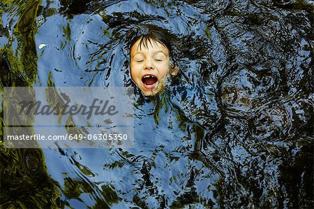 Laughing boy swimming in river Stock Photo - Premium Royalty-Free, Image code: 649-06305350